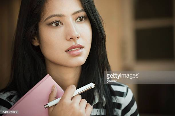 Indoor, serene Asian teenage girl student with book and pen.