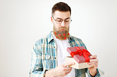 Indoor shot of bearded male model with long thick beard dressed in checkered shirt, opens present box, recieves surprise from girlfriend, isolated over white background. People and celebration.
