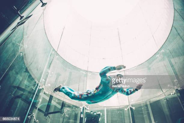 Indoors skydiving - one young man practising freefall simulation