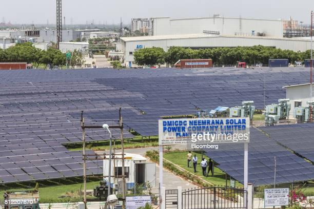 Industrial buildings stand beyond DMICDC Neemrana Solar Power Co's solar panels at the Rajasthan State Industrial Development and Investment...