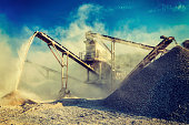 Vintage retro effect filtered hipster style image of Industrial background - crusher rock stone crushing machine at open pit mining and processing plant for crushed stone, sand and gravel
