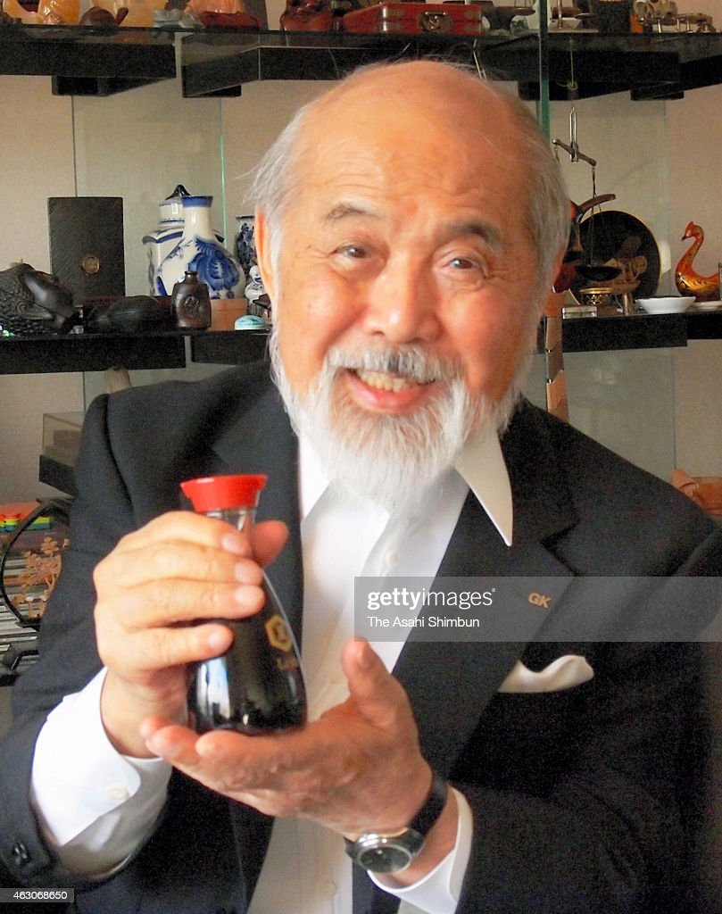 Industrial designer Kenji Ekuan poses for photographs with a iconic red-capped tabletop bottle for Kikkoman soy sauce at his office on October 25, 2012 in Tokyo, Japan.