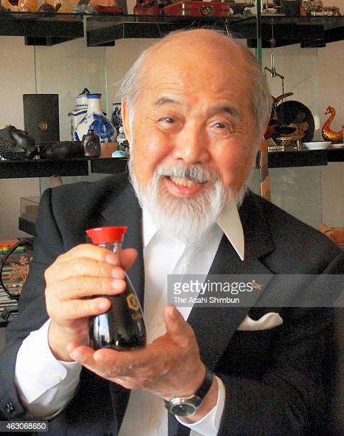 Industrial designer Kenji Ekuan poses for photographs with a iconic redcapped tabletop bottle for Kikkoman soy sauce at his office on October 25 2012...