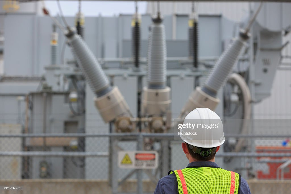 Industrial engineer examining high voltage transformer at a power plant