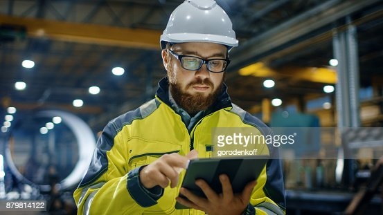 Industrial Engineer in Hard Hat Wearing Safety Jacket Uses Touchscreen Tablet Computer. He Works at the Heavy Industry Manufacturing Factory. : Foto stock