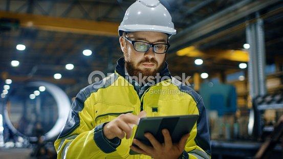 Ingeniero industrial en casco, con chaqueta de seguridad utiliza pantalla táctil Tablet PC. Trabaja en la industria pesada fábrica. : Foto de stock