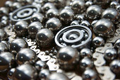 """Close-up of industrial bearings, chrome balls and metal chains."""