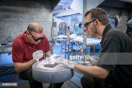 Industrial glass blowers constructing intricate glass part