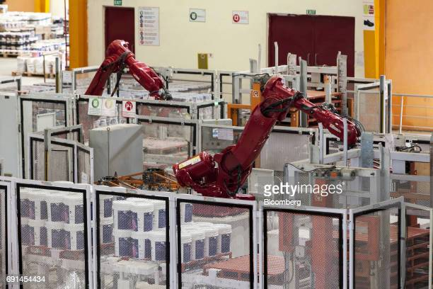 Industrial robots stack buckets of paint on pallets at an Akzo Nobel India Ltd paint factory in Gwalior Madhya Pradesh India on Thursday June 1 2017...