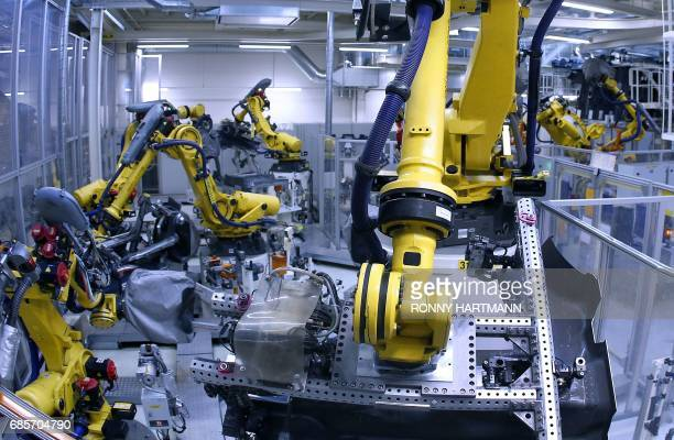 Industrial robots weld parts of chassis of the Volkswagen Golf 7 model at the Volkswagen car factory in Wolfsburg central Germany on May 19 2017...
