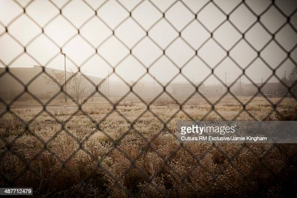 Industrial structures and abandoned land behind metal fence