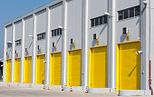 An industrial warehouse with eight large yellow drive-in doors for big trucks.