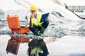 worker checking quality of material at an iron ore dump in an industrial area.