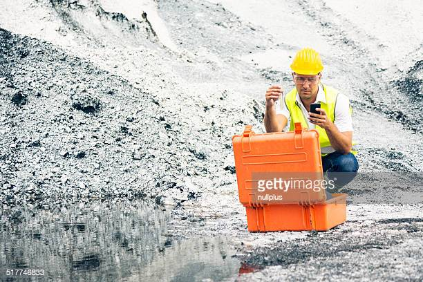 industrial worker checking quality of iron ore