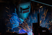 industrial worker is welding assembly car part in factory
