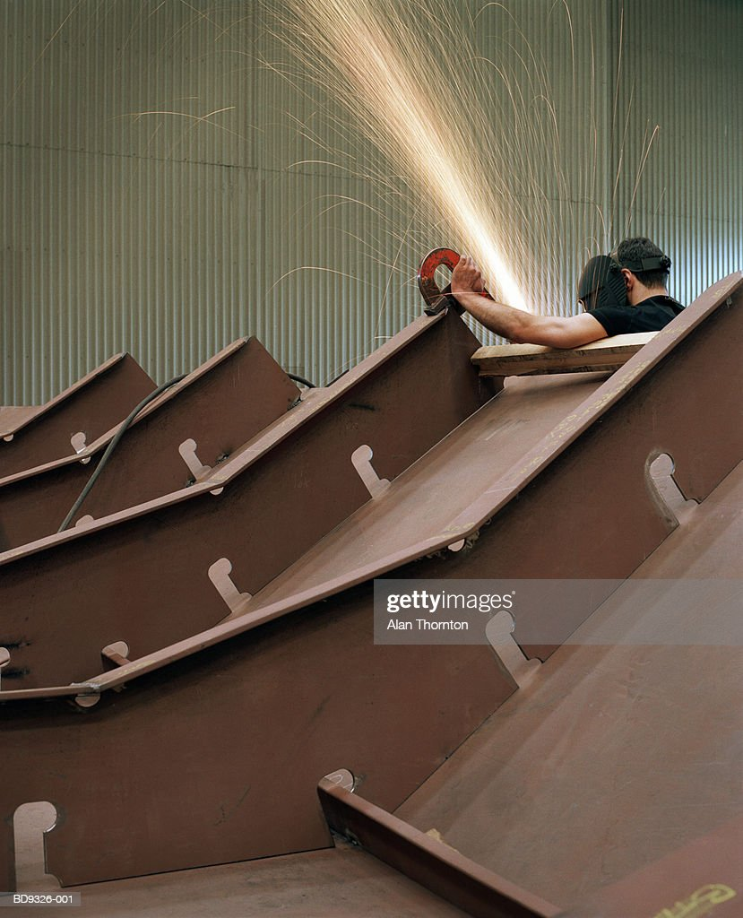 Industrial worker using grinder in shower of sparks : Stock Photo