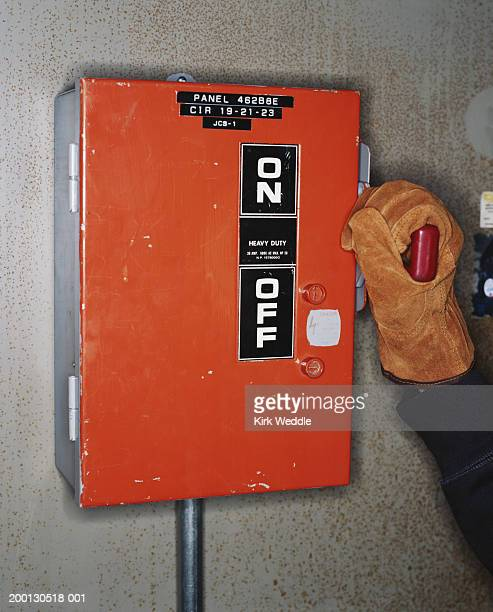 Industrial worker with gloved hand on handle of circuit breaker