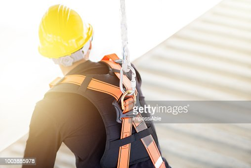 Industrial Worker with safety protective equipment loop and harness hanging at his back : Stock Photo