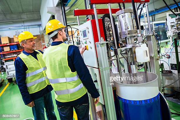 Industrial Workers Controling Machine in the Factory