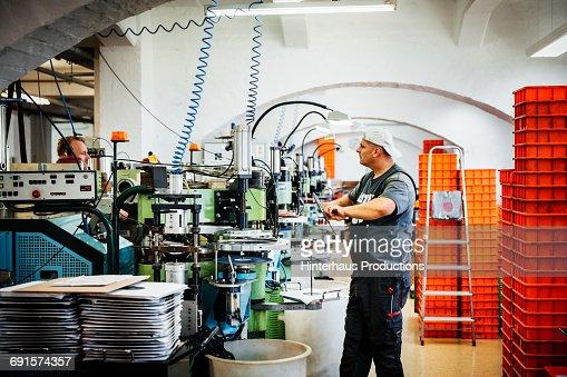 Industrial working standing between machines