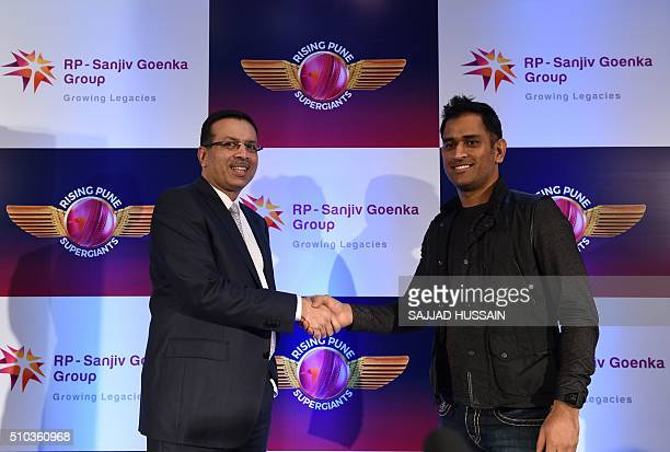 Industrialist and owner of the Indian Premier League's Rising Pune Supergiants cricket team Sanjiv Goenka shakes hands with team captain Mahendra...