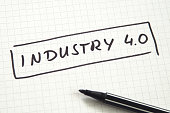 Industry 4.0 in handwriting on checkered paper with black felt pen