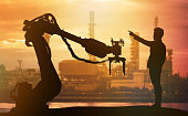 Industry 4.0 technology , artificial intelligence trend concept. Silhouette of business man point finger forward to heavy automation robot arm machine. Vivid sunset sky and smart factory background.