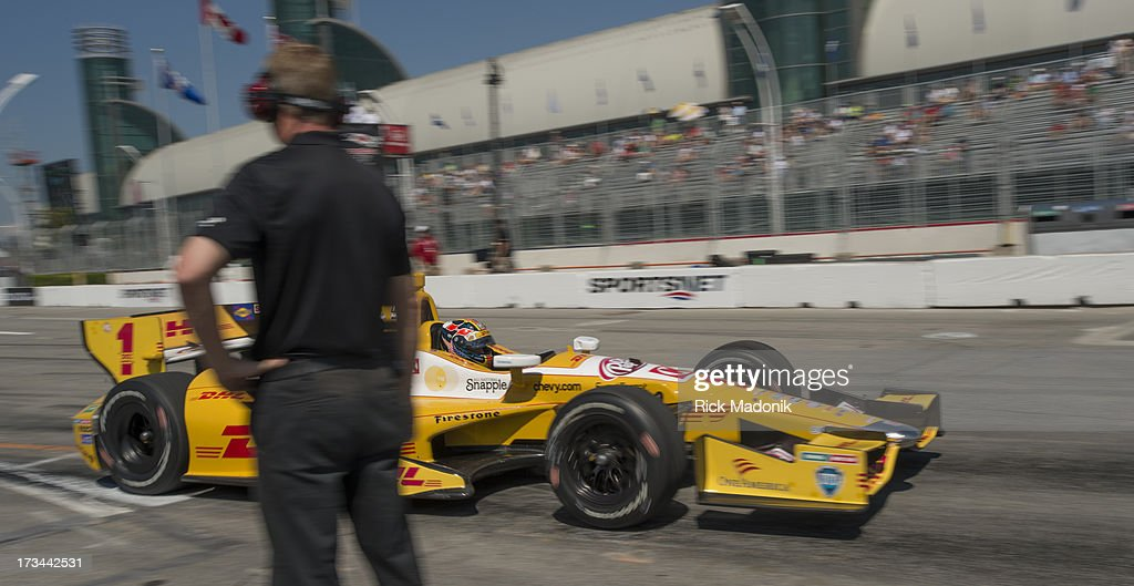 TORONTO, ON - JULY 14 - Indy cars practice the standing start at the end of Pit Row. Ryan Hunter-Reay speeds past a track official. Toronto Honda Indy is slated for a second attempt at a standing start in Toronto, on July 14, 2013.