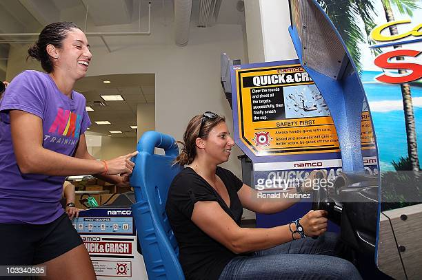 Indy Racing League driver Simona de Silvestro of Switzerland plays a racing video game with Christina Mchale during day two of the Western Southern...