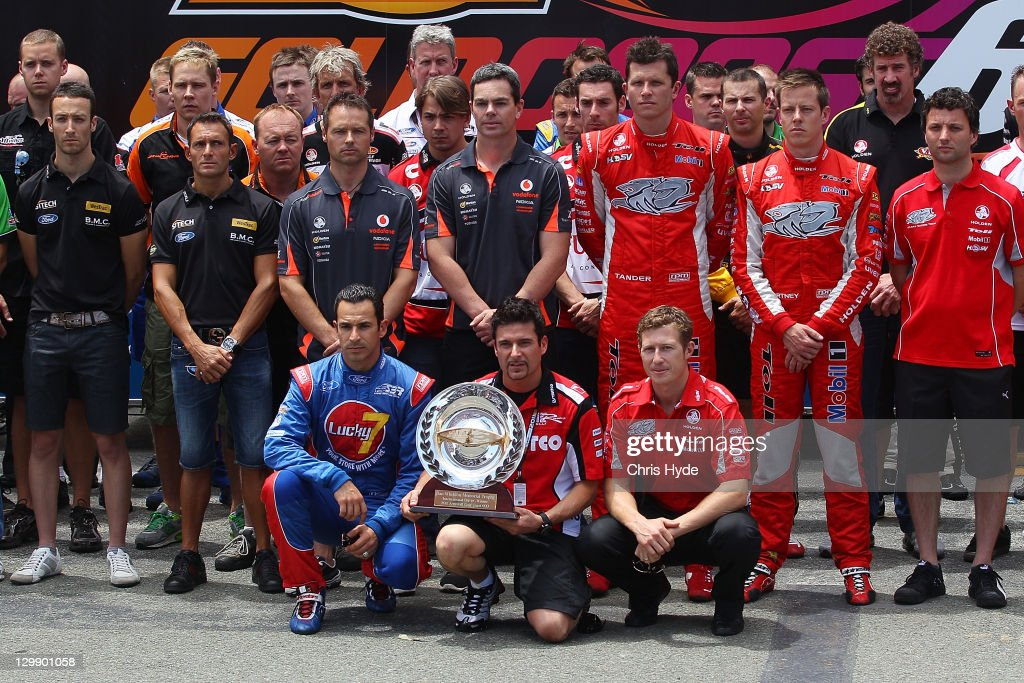 IndyCar drivers (L-R) <a gi-track='captionPersonalityLinkClicked' href=/galleries/search?phrase=Helio+Castroneves&family=editorial&specificpeople=201776 ng-click='$event.stopPropagation()'>Helio Castroneves</a>, <a gi-track='captionPersonalityLinkClicked' href=/galleries/search?phrase=Alex+Tagliani&family=editorial&specificpeople=220628 ng-click='$event.stopPropagation()'>Alex Tagliani</a> and <a gi-track='captionPersonalityLinkClicked' href=/galleries/search?phrase=Ryan+Briscoe&family=editorial&specificpeople=213207 ng-click='$event.stopPropagation()'>Ryan Briscoe</a> hold the Dan Wheldon Memorial Trophy during a tribute to the driver during the V8 Supercars Gold Coast 600 at the Gold Coast Street Circuit on October 22, 2011 on the Gold Coast, Australia. British driver Wheldon was killed in a 15 car pile-up during a race at Las Vegas on October 16, 2011.
