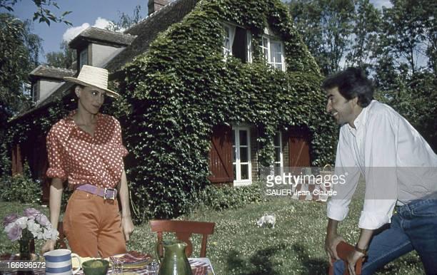 Ines De La Fressange And Her Husband Luigi D'Urso In Normandy Inès DE LA FRESSANGE coiffée d'un chapeau de paille avec son mari Luigi D'URSO devant...