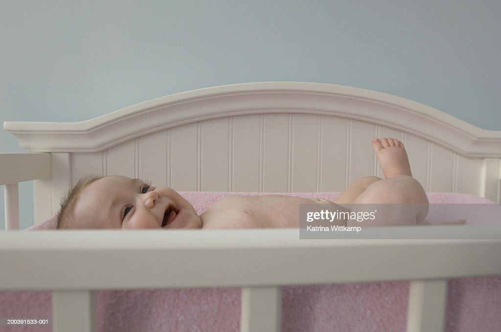 Infant baby girl (6 months old) lying in crib, laughing : Stock Photo