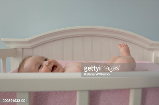 Infant baby girl (6 months old) lying in crib, laughing : Foto de stock