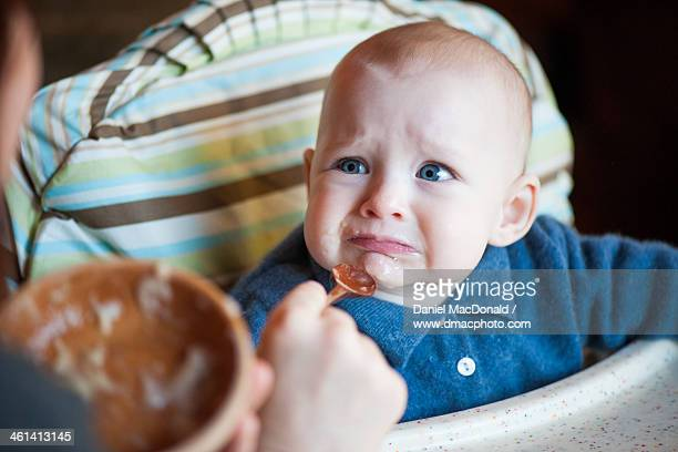 Infant baby girl not sure about first solid food