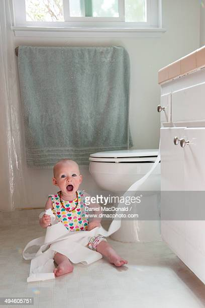 Infant baby girl playing with toilet paper