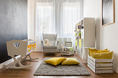 Lovely trendy nursery room with white minimalist furniture