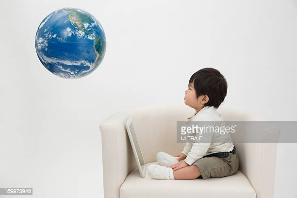 Infant boy looking at a globe