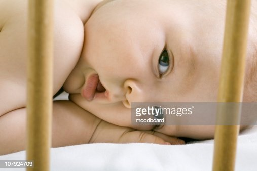 Infant child lying in cot : Stock Photo