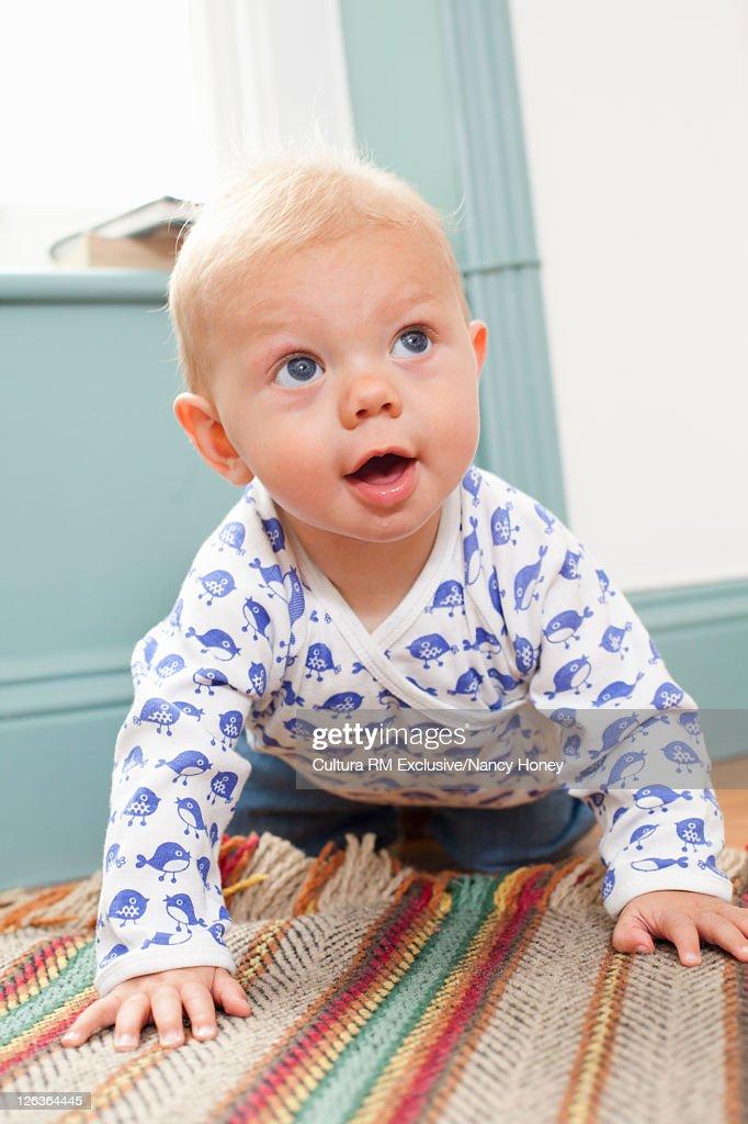 Infant crawling on bathmat : Stock Photo