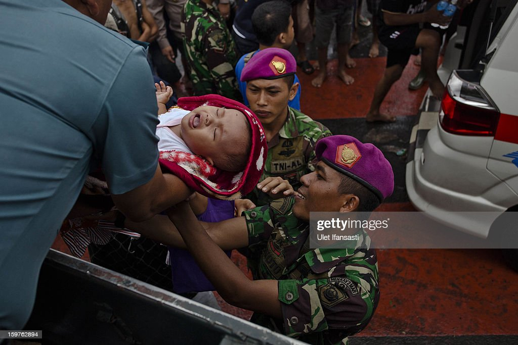 Infant Mutiara Rahmadani is evacuated by Indonesian Army as major floods hit North Jakarta on January 20, 2013 in Jakarta, Indonesia. The death toll has risen to at least 21 since severe flooding struck the city on January 17. The US has offrered US$150,000 (Rp 1.44 billion) in aid.