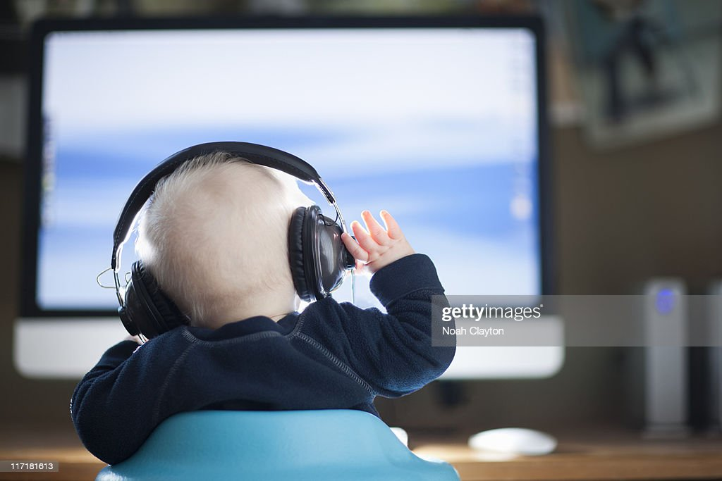 Infant sits in front of computer wearin headphones : Stock Photo