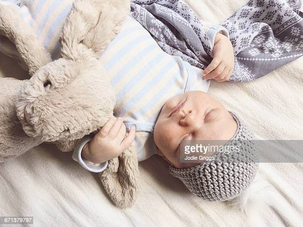 Infant sleeping peacefully with teddy and blanket