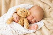 Infant sleeping together with teddy bear