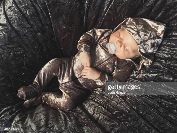 Infant wearing a shiny velour romper sleeping peacefully