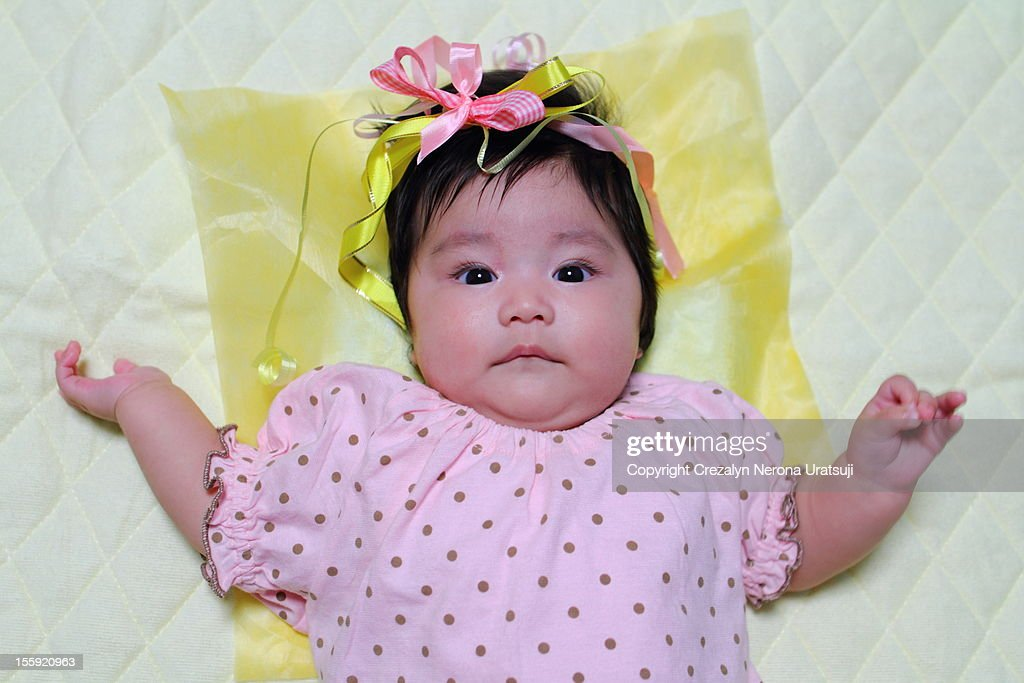 Infant with gift ribbon on head : Stock Photo