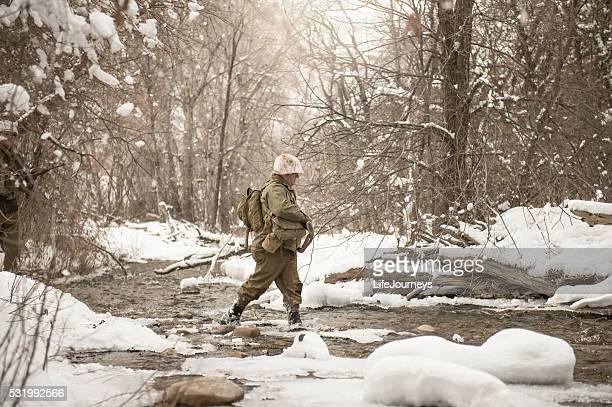 WWII US Infantry Soldier Crossing A Creek In Winter
