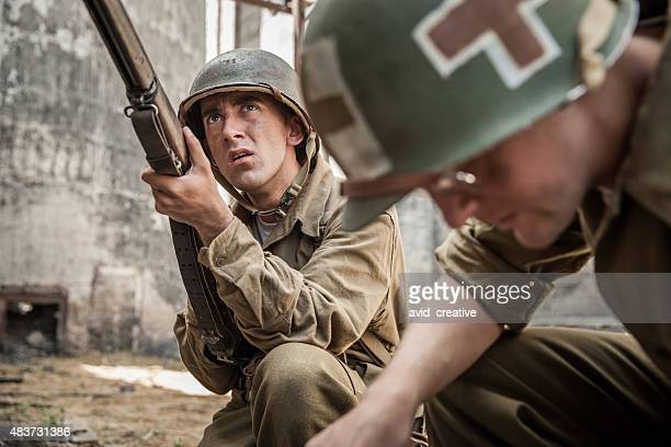 WWII Infantry Soldier Guards Medic Administering First Aid to Fa