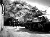 Infantrymen and a tank of the 11th Armored Division 3rd US Army advances through a smokefilled street in Wernberg April 22 1945