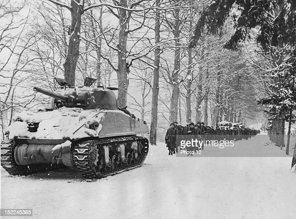 Infantrymen and tanks of the 75th US Division move forward over a snowcovered road on the northern flank of the Ardennes salient