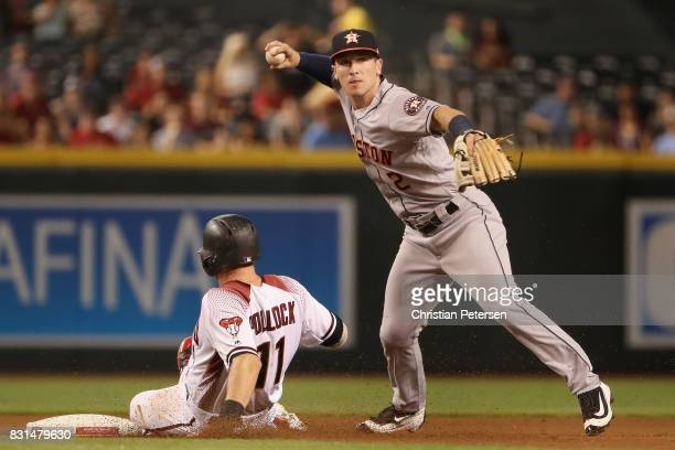 Infeilder Alex Bregman of the Houston Astros throws over the sliding AJ Pollock of the Arizona Diamondbacks to compete a double play during the first...